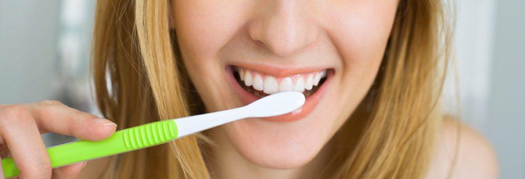smiling women brushing her teeth